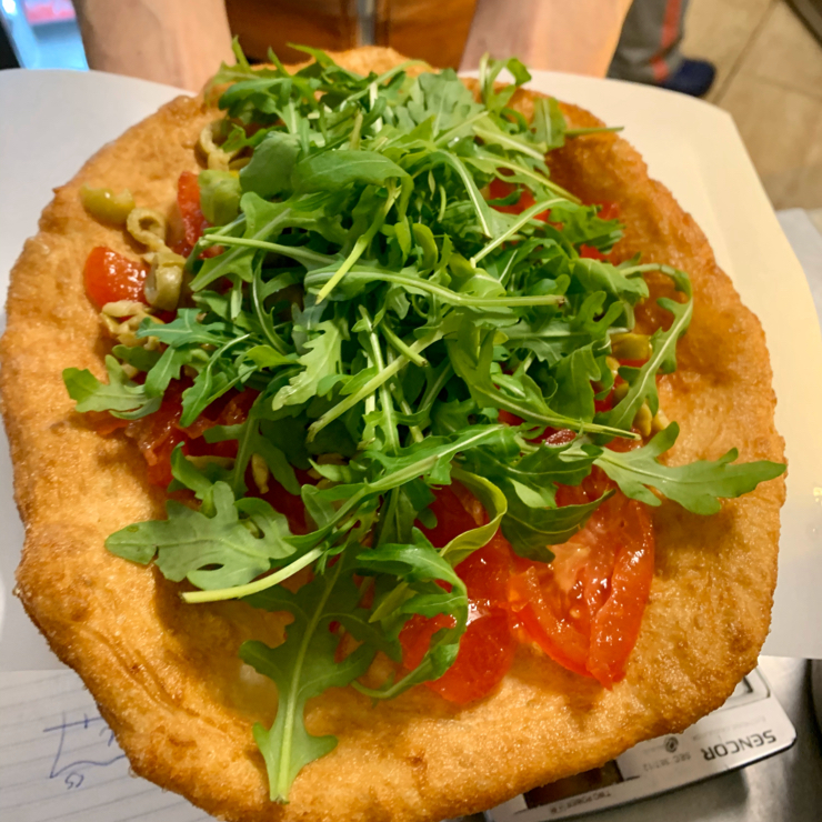 Vegan user review of Retró Lángos Büfé in Budapest. Langot is the traditional Hungarian dish of fried pizza dough (vegan) with toppings. Retro Lsngos understands what Vega is and can customize your labgos with vegan toppings such as mushrooms, peppers, olives, tomatoes and arugula.